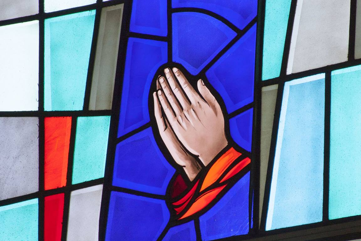 Stained glass window of hands praying. Photo by Jan Snider, United Methodist Communications.