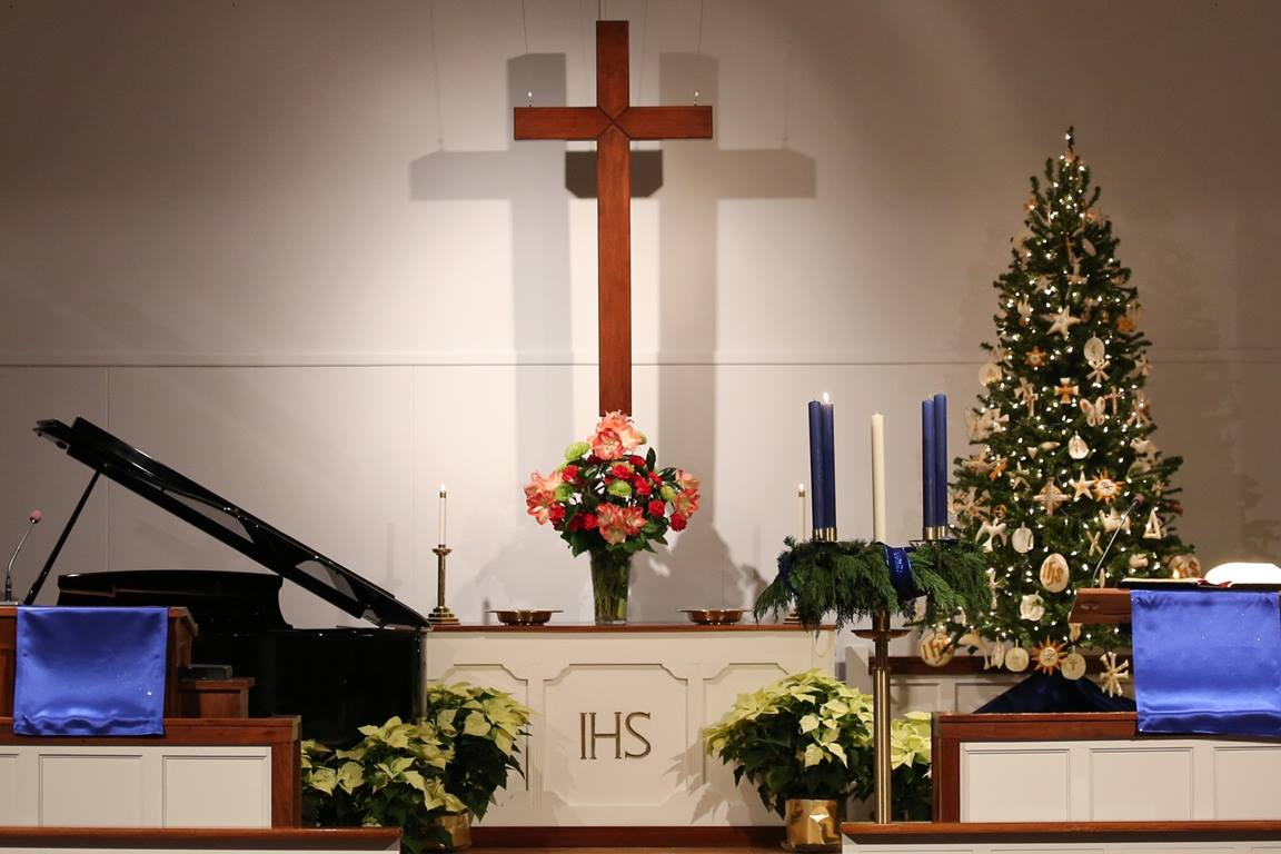The Glendale United Methodist Church sanctuary in Nashville, Tennessee, is decorated for Advent with symbols of the season, including poinsettias and a Christmas tree.