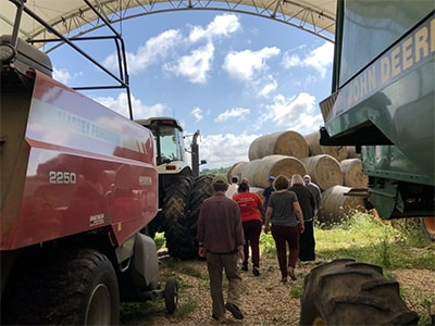 Members take a tour of a farm with large equipment. Courtesy photo.