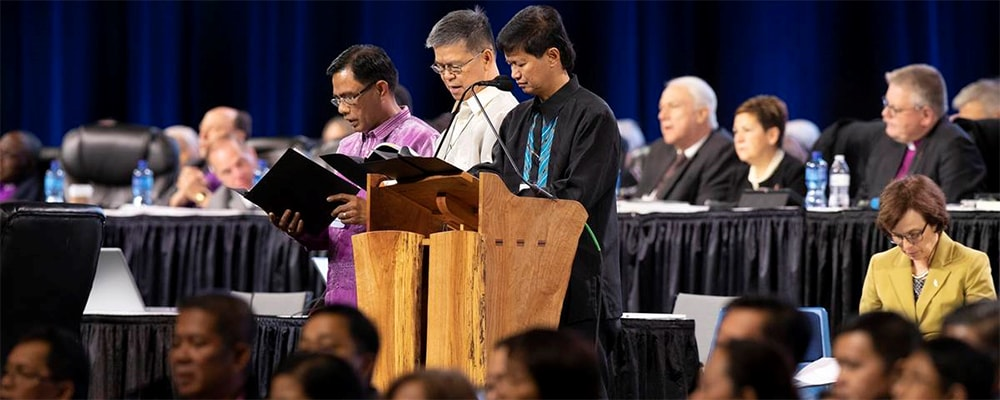 """Bishops Rodolfo Alfonso """"Rudy"""" Juan (left), Ciriaco Q. Francisco (center) and Pedro M. Torio Jr. lead a prayer for the Philippines and Southeast Asia during the 2019 United Methodist General Conference in St. Louis in February. The Philippines Central Conference College of Bishops, meeting in Manila, signed a resolution opposing dissolution of The United Methodist Church. File photo by Kathleen Barry, UM News."""