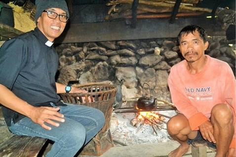 The Rev. Frankie Ortilano Cayaban visits in the home of a resident along his circuit in the Philippines.