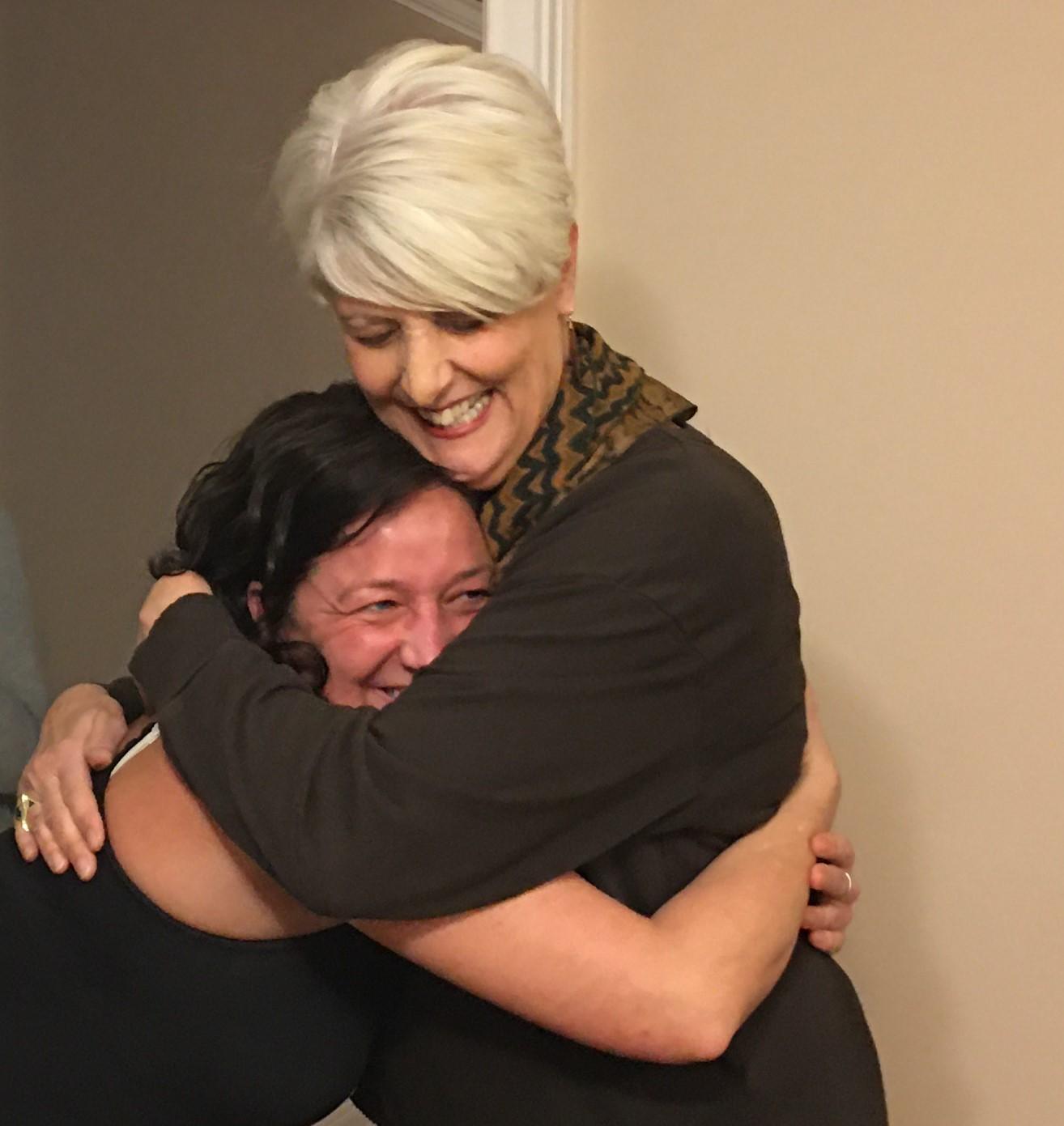 Volunteer Pat Ralls (top) hugs a Healing Housing resident.