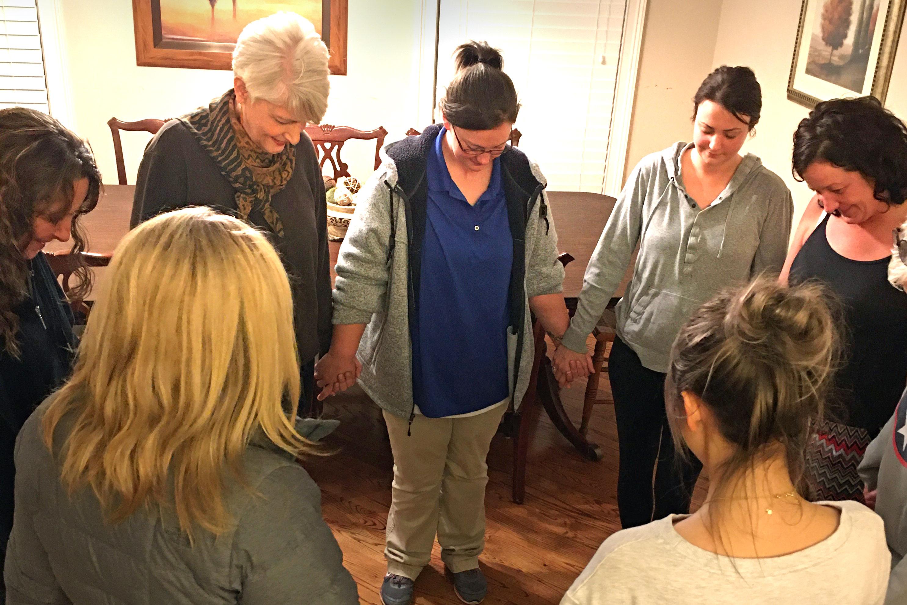 Voluntaria Pat Ralls  (pelo blanco, a la izquierda) dirige a las residentes de Healing Housing (casa de sanidad) en oración. Foto cortesía de Healing Housing.