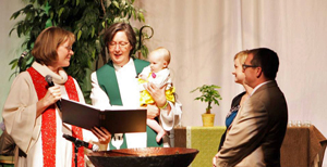 Baptism unites us as a community of faith, as Bishop Elaine J.W. Stanovsky illustrated in the baptism of the daughter of two elders during the 2013 Rocky Mountain Annual Conference. File photo, United Methodist Communications.