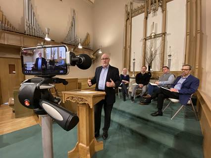 The Rev. Eric Folkerth, senior pastor of Kessler Park United Methodist Church in Dallas is recorded with a cell phone during a service March 15. The church is livestreaming their services on Facebook due to the coronavirus or COVID0-19. Photo by Brett Shipp, courtesy of Kessler Park United Methodist Church.