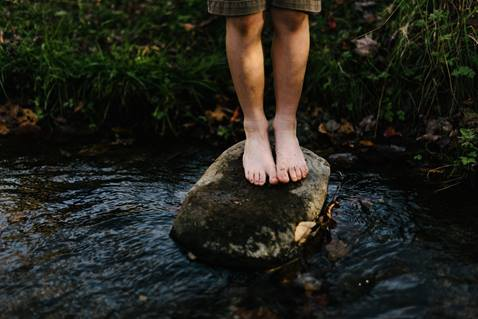 A person stands on a stepping stone in a stream. Photo by Jordan Whitt on Unsplash