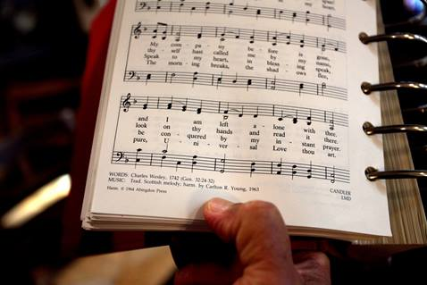 """The Rev. Romero del Rosario holds a songbook featuring the lyrics written by Charles Wesley in 1742, """"Come, O Thou Traveler Unknown."""" Photo by Kathleen Barry, UM News."""