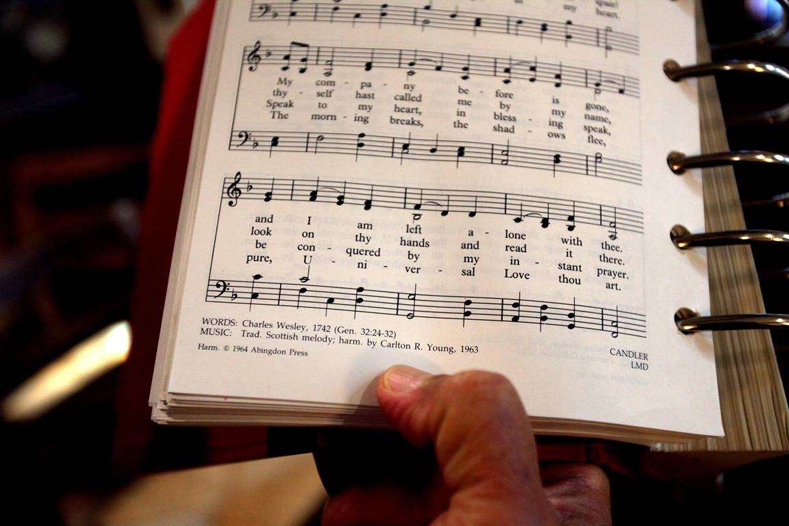 "The Rev. Romero del Rosario holds a songbook featuring the lyrics written by Charles Wesley in 1742, ""Come, O Thou Traveler Unknown."" Photo by Kathleen Barry, UM News."