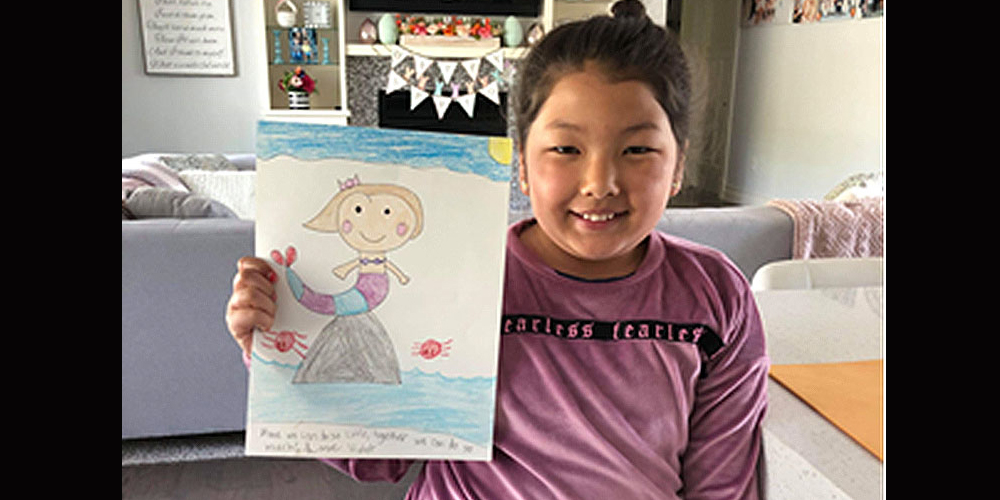 Violet, an Illinois third-grader and a member of Grace UMC in Carbondale, holds up her drawing.