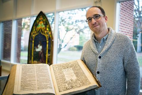 """Archivist Brian Shelter shows a rare first edition King James """"He"""" Bible in the Drew collection."""