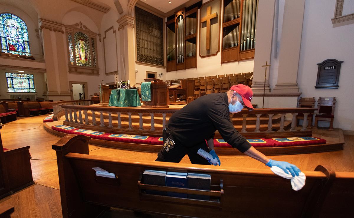 """El custodio James Jimmerson desinfecta los bancos para evitar la posible propagación del COVID-19 en la IMU Belmont en Nashville, Tennessee, después de la adoración en línea que se grabó en el santuario el domingo 10 de mayo de 2020. A medida que las iglesias consideran regresar a la adoración en persona, las medidas de limpieza son uno de los muchos factores que los/as líderes deberán considerar. """"Creo que mi trabajo es asegurarme de que las personas estén seguras aquí"""" dijo Jimmerson. Foto de Mike DuBose, Noticias MU."""