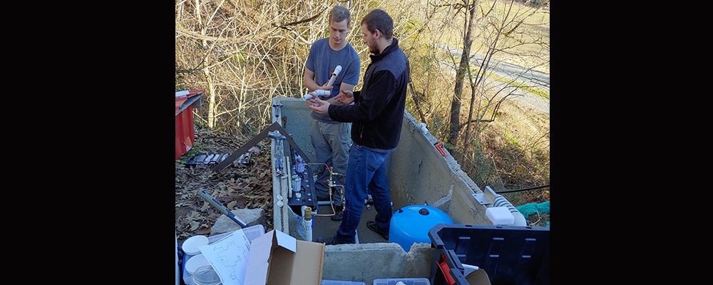 Two senior mechanical engineering students, Sterling Burnett (short-sleeves) and Jonathan Wyatt (long sleeves) install a water treatment system that includes filtration, Ultraviolet Light disinfection, and activated carbon filtration to improve the water quality for the community at Cedar Grove spring.