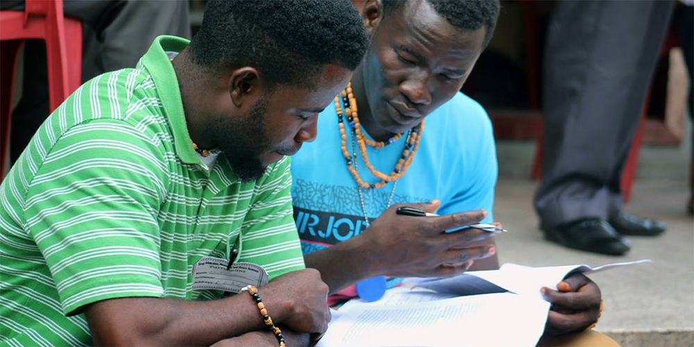Eric Nyenow (left) and Emmanuel Gbuie, residents of the United Methodist New Life Recovery Center, review their notes during an addiction and substance abuse seminar in Monrovia, Liberia. The United Methodist Church in Liberia hosted the seminar to help local churches expand and strengthen their recovery ministries.