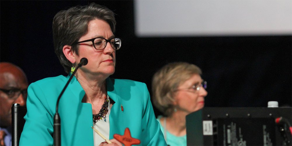 Bishop Sally Dyck presides over a discussion of the church budget during the 2016 United Methodist General Conference in Portland, Ore. With the next General Conference delayed until 2021, the board of the denomination's finance agency decided it had no choice but to continue with the apportionment formula approved in 2016.