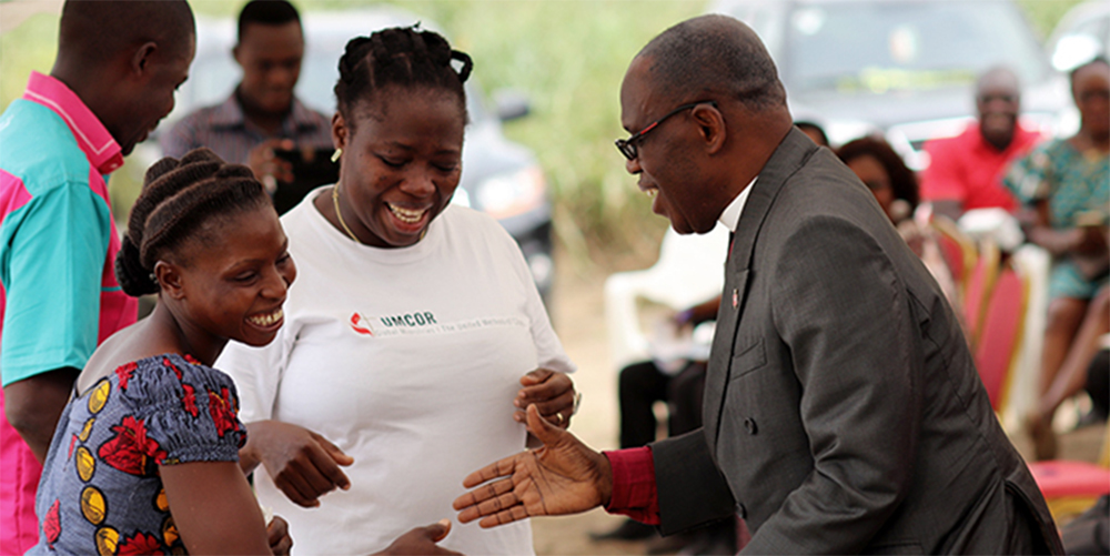 Bishop Benjamin Boni, Côte d'Ivoire Episcopal Area (right), congratulates Angèle Seri, deputy president of United Methodist Women in Issia, during the Jan. 11 inauguration of an attiéké processing plant in Anyama, Côte d'Ivoire. In the middle is Gisèle Koké, project coordinator for le Réservoir de Siloé, the United Methodist organization that built the plant.