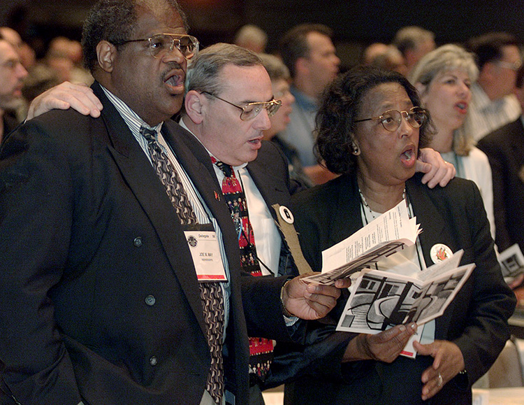 Mississippi Conference delegates (from left) Joe W. May, Larry M. Goodpaster and Dora S. Washington sing together during a service of repentance for racism within The United Methodist Church during 2000 General Conference in Cleveland. File photo by Mike DuBose, UM News.
