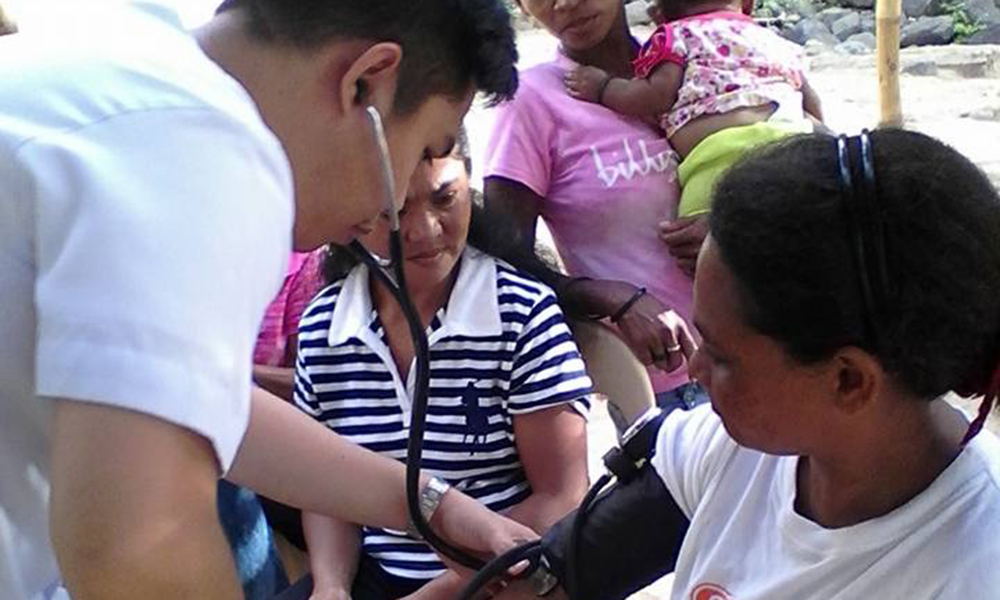 Dr. Karl Wesley E. Dillozon checks the blood pressure of a patient.