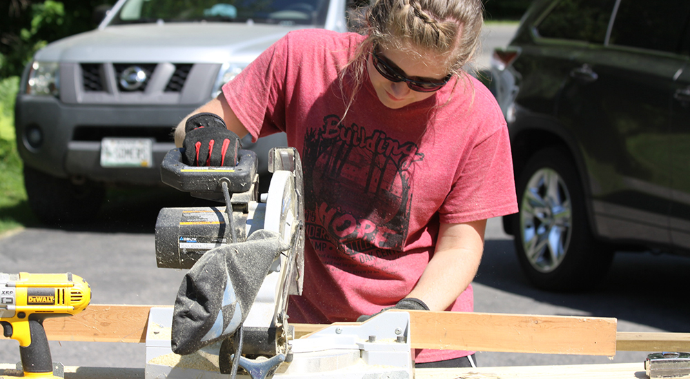 Joslyn Juhl works with table saw at community project.