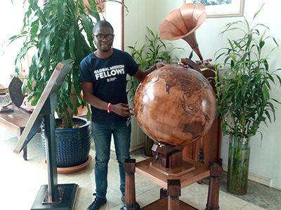 WCS Scholar stands next to Globe. Courtesy photo.