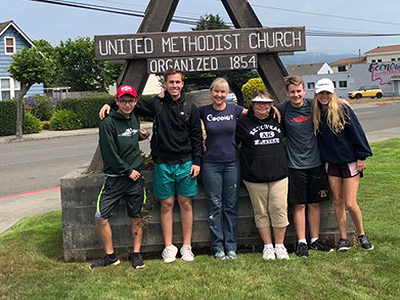 Trent Hisey, second from left,  poses with youth group in front of congregation sign.