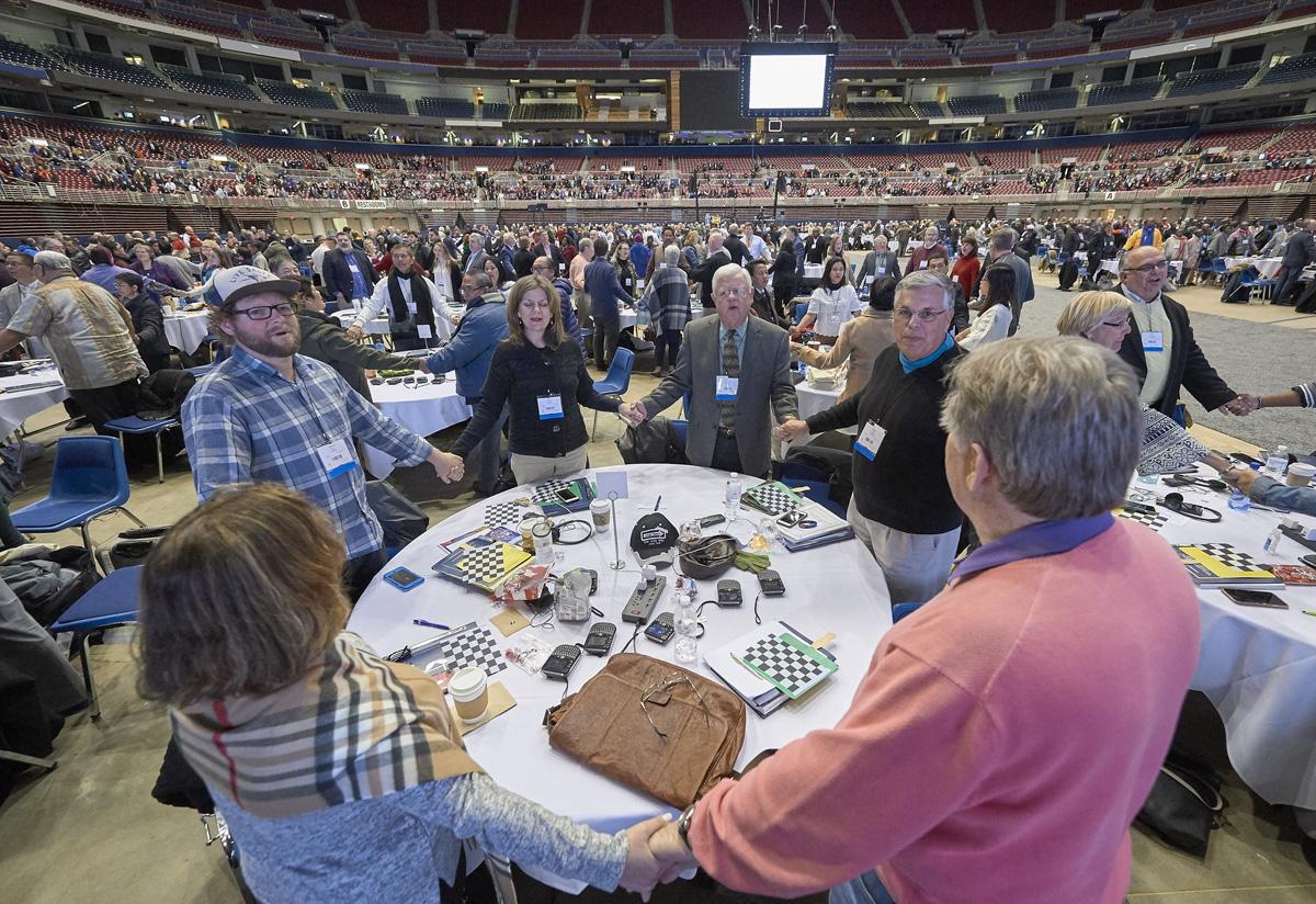 Os delegados dão as mãos e oram em 23 de fevereiro de 2019, no plenário de abertura da sessão extraordinária da Conferência Geral realizada em St. Louis. Foto de arquivo de Paul Jeffrey, Notícias MU.
