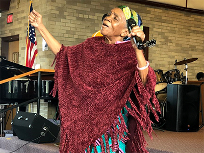 A woman offers a heart-felt prayer during worship at Restoration Community Church, an African congregation hosted by Wesley Park UMC in Wyoming, MI. ~ photo courtesy Dean Prentiss