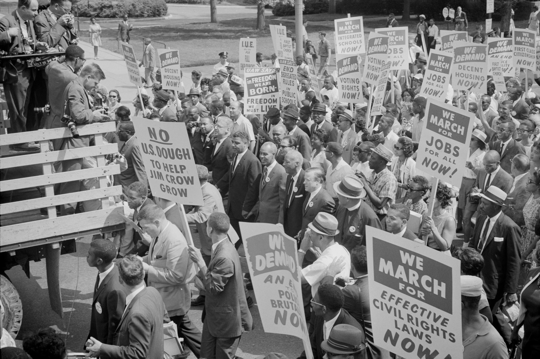 Des leaders des droits civiques, dont Martin Luther King, Jr., entourés de foules portant des pancartes lors de la marche sur Washington pour l'emploi et la liberté, le 28 août 1963. Photo de la Bibliothèque du Congrès.