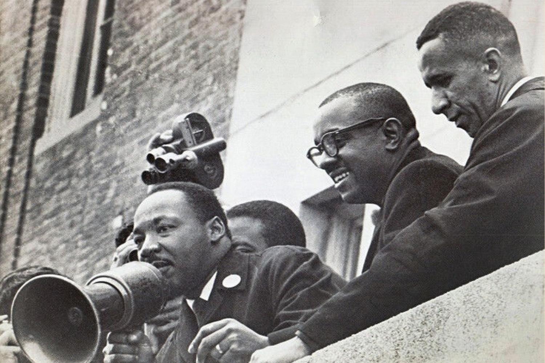 Le Rév. Gilbert H. Caldwell (à droite) se tient aux côtés des Rév. Martin Luther King Jr. (à gauche) et Virgil Wood sur le toit d'une école publique de Boston en 1965. Photo gracieuseté du révérend Gilbert H. Caldwell.