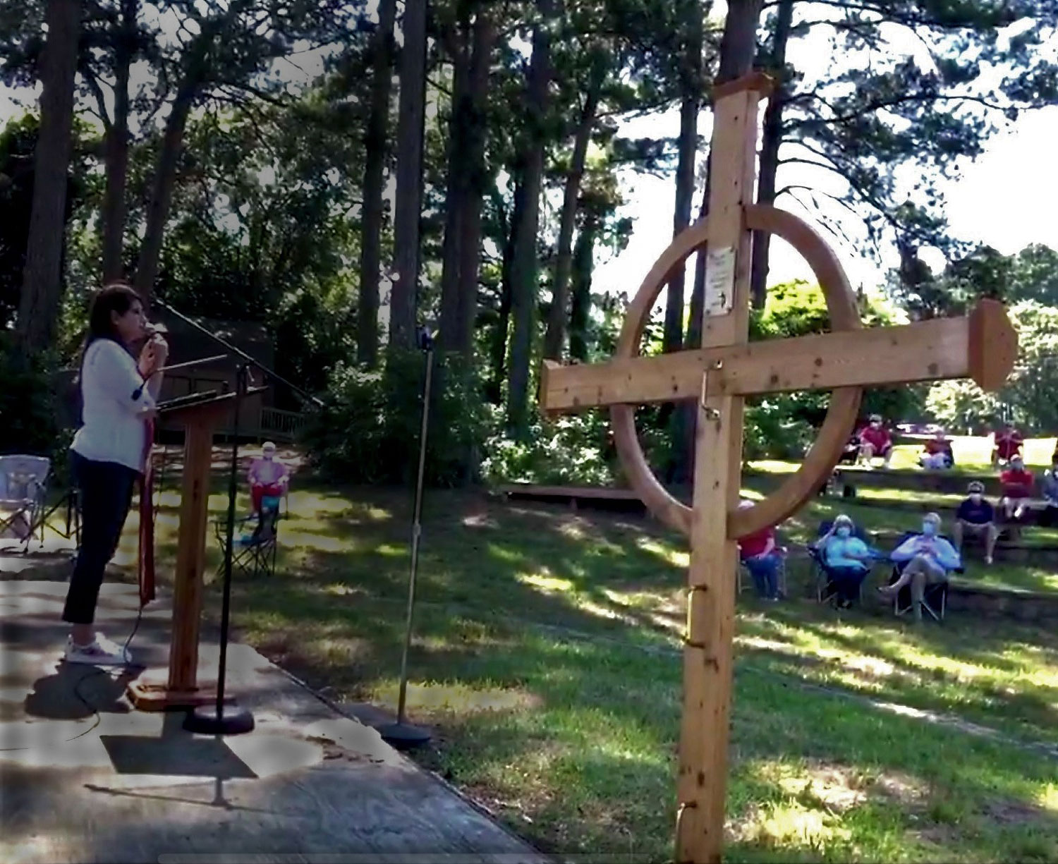Members of Lake Palestine United Methodist Church worship outdoors from a safe physical distance.