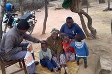The Rev. Paul Nyagomo (left), pastor in charge of four United Methodist churches in the Marange District, visits with 79-year-old Agness Takodza in Mutare City, Zimbabwe, after delivering her medication. Seated with Takodza are her grandchildren, Nomsa (6) and Lessley (7), and Gift Takodza. Photo by Kudzai Chingwe, UM News.