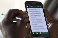 United Methodist Communicator Phileas Jusu reads a Bible verse on his mobile device in Freetown, Sierra Leone. Photo by Mike DuBose, UMNS.