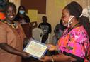 Oretha Goyanvator receives a certificate during training led by United Methodist Women in Monrovia, Liberia. As part of the new Village Saving Scheme program, participants learned to make soap, detergent and sanitary pads to help them earn and save money during the COVID-19 pandemic. Photo by E Julu Swen, UM News.