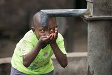 Joseph Ekow, 5, catches the final trickle of water after filling his bucket at a well behind John Kofi Asmah United Methodist Church in the West Point neighborhood in Monrovia, Liberia. Many families in this dense, urban area lack access to piped water. Photo by Mike DuBose, UM News