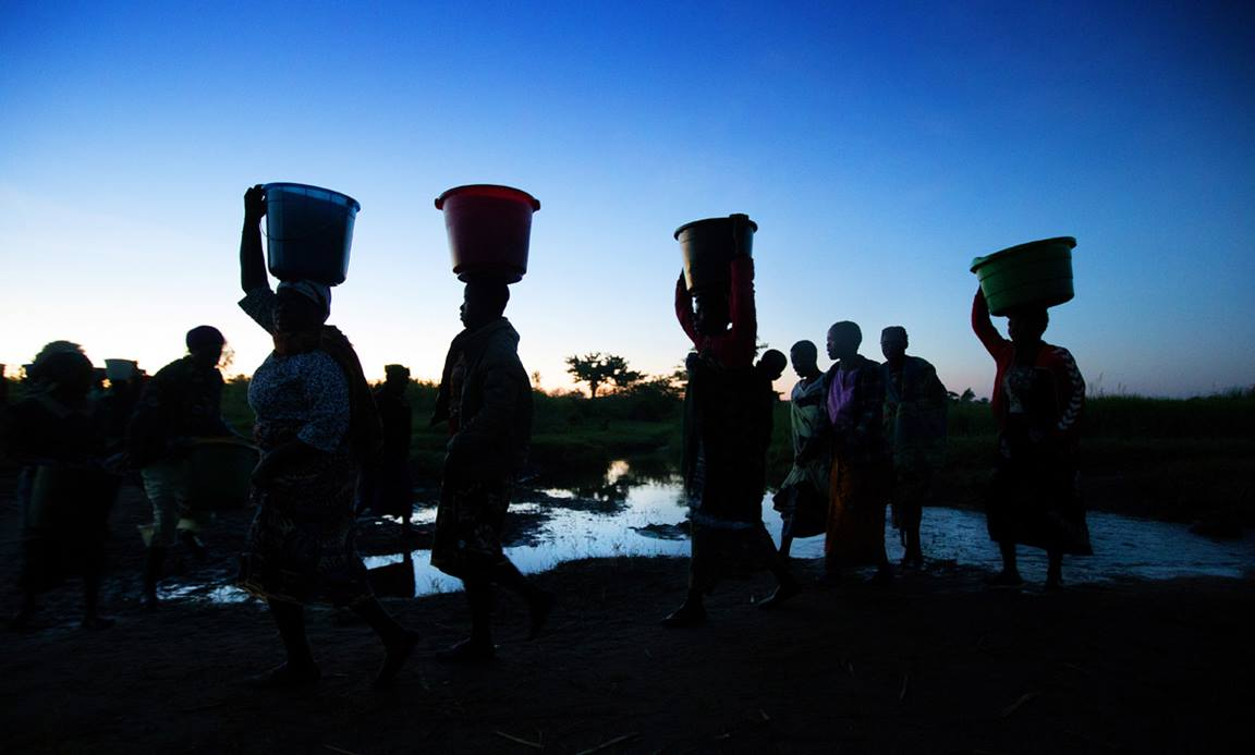 Women carry water as the sun rises at Njenjete village near Madisi, Malawi. Photo by Mike DuBose, UM News.