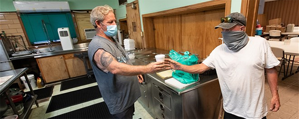Regular volunteer Scott Colon (left) offers coffee to Randall Wood in the kitchen at Galveston (Texas) Central Church. The United Methodist church opens its doors to community members, many of whom are experiencing homelessness. The church provides a safe space and a variety of services, including internet access, meals, showers and laundry facilities. Photo by Mike DuBose, UM News.
