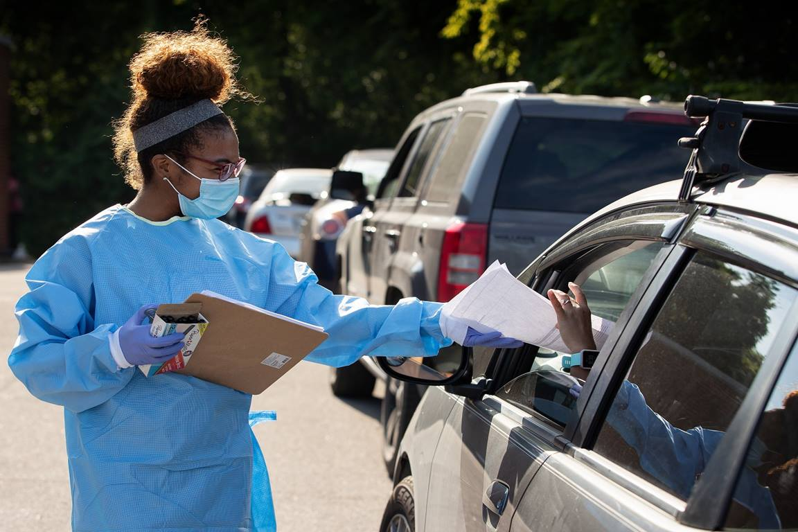 Tamera Thomas hands out paperwork to people waiting for a COVID-19 test at a drive-thru site offered by Meharry Medical College at St. Luke Christian Methodist Episcopal Church in Nashville, Tenn. Thomas, part of an all-volunteer team, is a dental student at the United Methodist-related medical school. Photo by Mike DuBose, UM News..