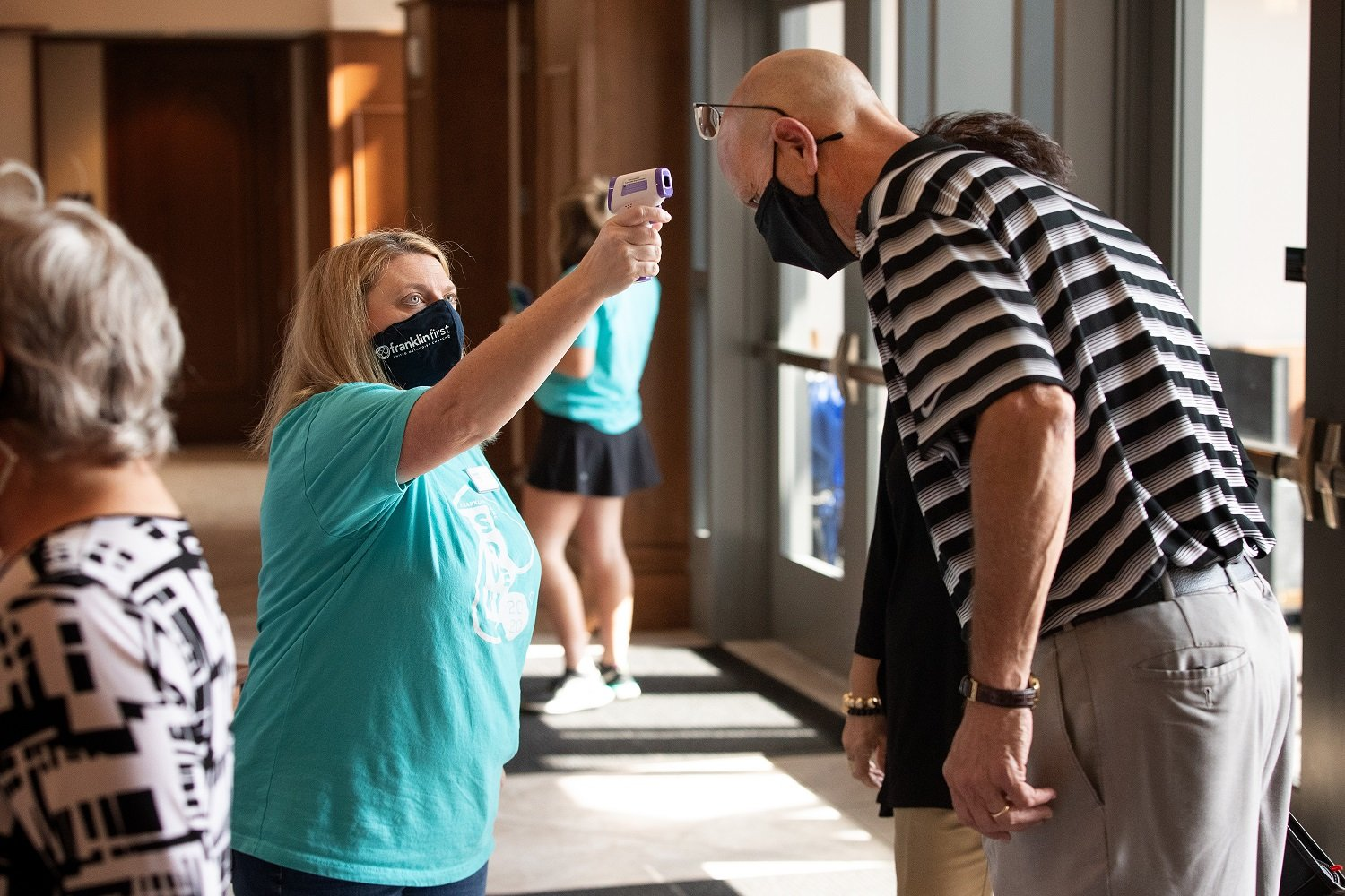 Volunteer Jennifer Jannetty checks James Crigger's temperature as he arrives for worship at Franklin (Tenn.) First United Methodist Church. The church, which recently returned to in-person worship, has adopted safety protocols to help prevent the possible spread of COVID-19. Photo by Mike DuBose, UM News.