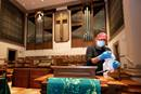 """Custodian James Jimmerson disinfects a microphone to prevent any possible spread of the coronavirus at Belmont United Methodist Church in Nashville, Tenn., on Sunday, May 10, following online worship, which is recorded in the sanctuary. As churches considered returning to in-person worship, cleaning measures are one of many factors leaders considered. """"I believe my job, my part in this, is to make sure people are safe in here,"""" Jimmerson said. File photo by Mike DuBose, UM News."""