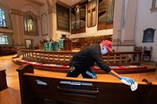 Custodian James Jimmerson disinfects pews to prevent any possible spread of the coronavirus at Belmont United Methodist Church in Nashville, Tenn., on Sunday, May 10, 2020, following online worship, which is recorded in the sanctuary. Photo by Mike DuBose, UM News.