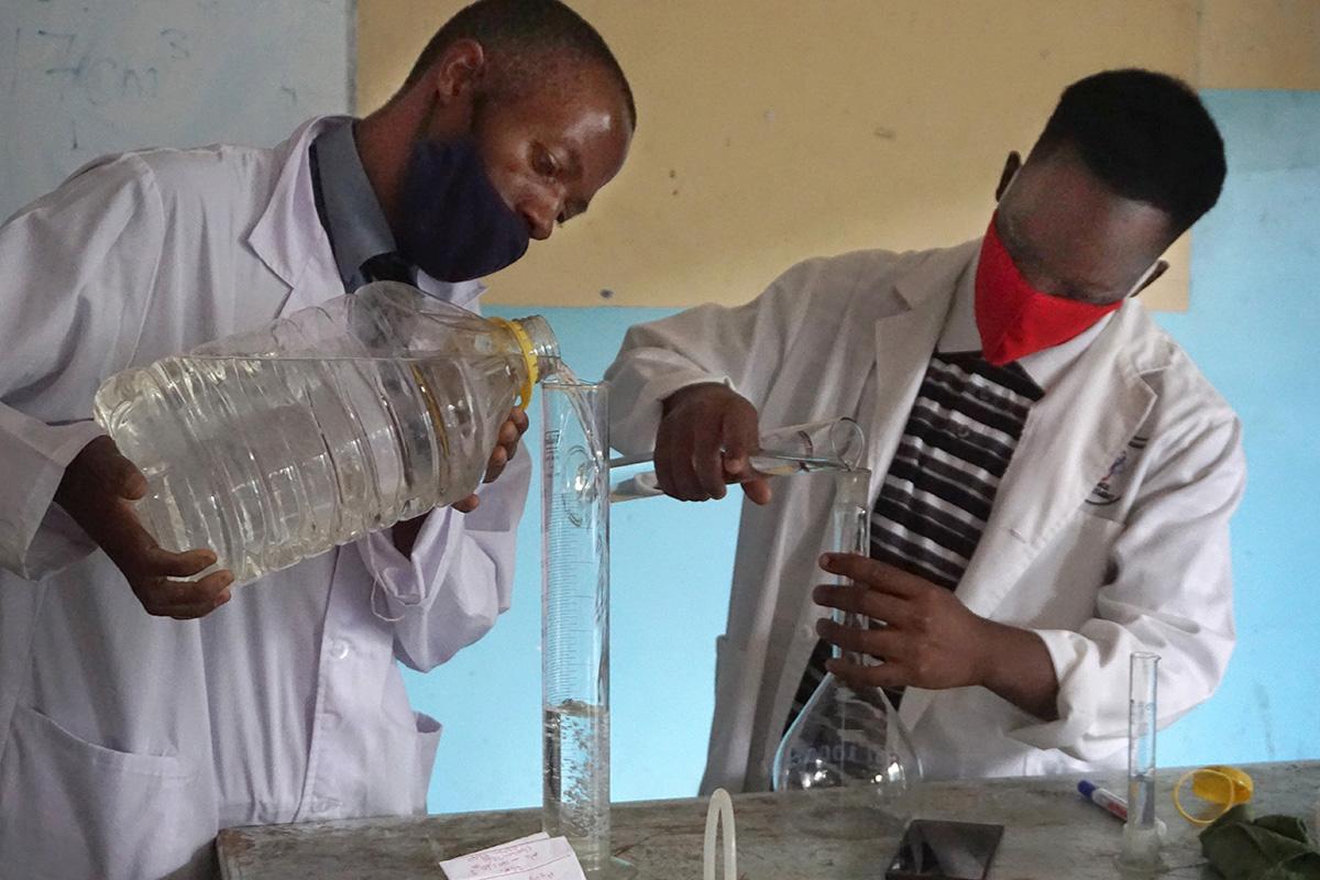 """Innocent Mushayavanhu (left) and Tariraishe Mubazangi prepare hand sanitizer at The United Methodist Church's Murewa High School in Murewa, Zimbabwe. """"We managed to prepare ministerial-approved sanitizers and face masks for the school of 1,250 learners, 30 workers and 55 teachers,"""" said Sydney Mapisaunga, the school's headmaster. Photo by Kudzai Chingwe, UM News."""