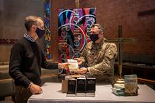 "The Rev. Tom Berlin (left) presents a copy of his book, ""Courage,"" to Massachusetts National Guard Chaplain Chad McCabe in the chapel at Wesley Theological Seminary in Washington. McCabe, whose unit was assigned to help provide security at the U.S. Capitol after the January riot, contacted Wesley Seminary asking for Bibles, novels and board games for troops stationed there. Photo by Lisa Helfert for Wesley Theological Seminary. Copyright 2021. All rights reserved. Used with permission."
