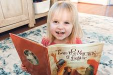 """Finley Howell, 3, daughter of Shawn Howell and the Rev. Ricky Howell of Water's Edge United Methodist Church in Beaufort, S.C., enjoys """"Twas the Morning of Easter"""" by Glenys Nellist. Photo by Shawn Howell."""