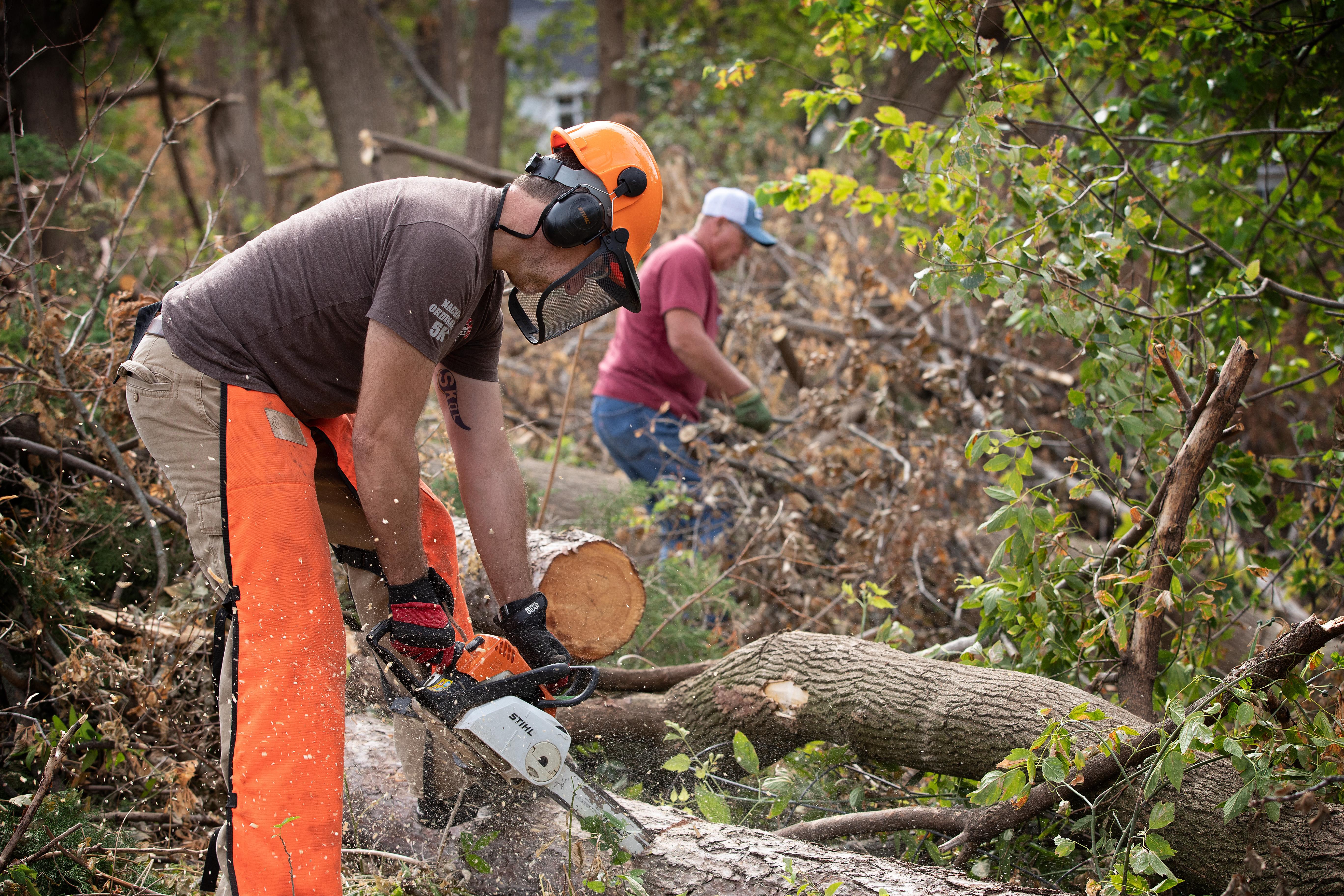 Os voluntários Metodistas da United Darren Garrett (frente) e Dale Krohn usam motosserras para limpar árvores derrubadas em uma casa em Cedar Rapids, Iowa, após um vendaval em Agosto de 2020. Foto de Mike DuBose, UM News.