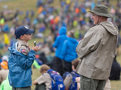 """A Scout shows his copy of the United Methodist devotional guide """"Strength for Service"""" to an adult leader at the 2017 National Scout Jamboree at the Summit Bechtel Reserve in Glen Jean, W.Va. The General Commission on United Methodist Men supports Scouting and publishes the """"Strength for Service"""" devotional series. File photo by Mike DuBose, UM News."""
