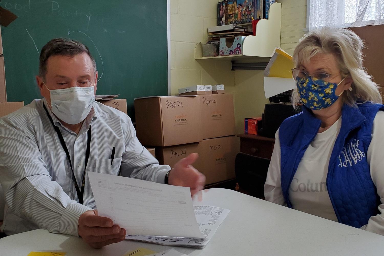 Dan Molnar (left) of Muldraugh United Methodist Church assists a client with tax return preparation through the Internal Revenue Service's VITA program. Photo by Melissa Molnar.