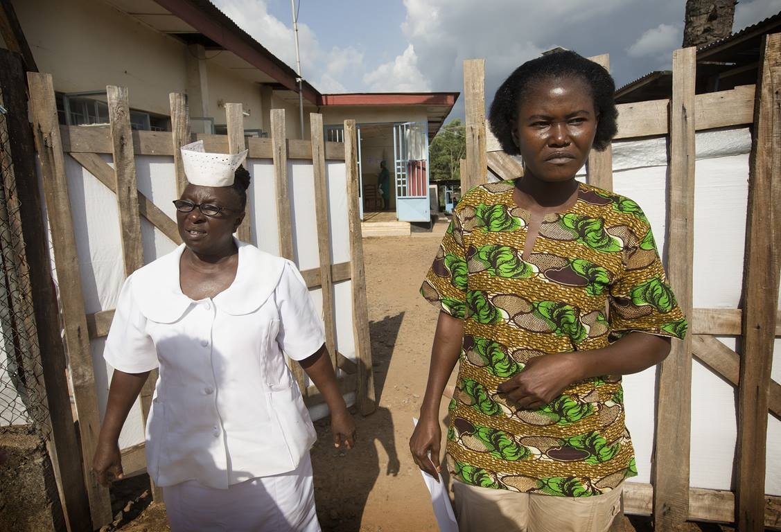 Mbalu Fonnie, head nurse in the hemorrhagic fever ward, and nurse Veronica Karoma describe efforts to contain the Ebola virus as they stand outside the gates to the isolation ward at the government hospital in Kenema, Sierra Leone. Photo by Mike DuBose, UM News.