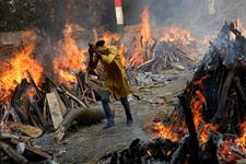 A man runs past the burning funeral pyres of people who died from COVID-19, during a mass cremation at a crematorium in New Delhi, India. The escalating crisis in India will be addressed by The United Methodist Church through grants to entities there who have been partners in the past. Photo by Adnan Abidi, Reuters.