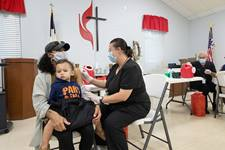 Camisha Henson holds her son Welles in her lap while receiving a COVID-19 vaccination from Tabitha England, RN, during a clinic at St. Mark's United Methodist Church in Charlotte, N.C.