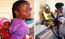 Left: Animata holds tight to her dad in the Sierra Leone Hospital where she received her malaria treatment. Right: Amelia Toe receives malaria medicine at the United Methodist John Dean Town Clinic in Liberia. Photos: Health Boards of Sierra Leone and Liberia.