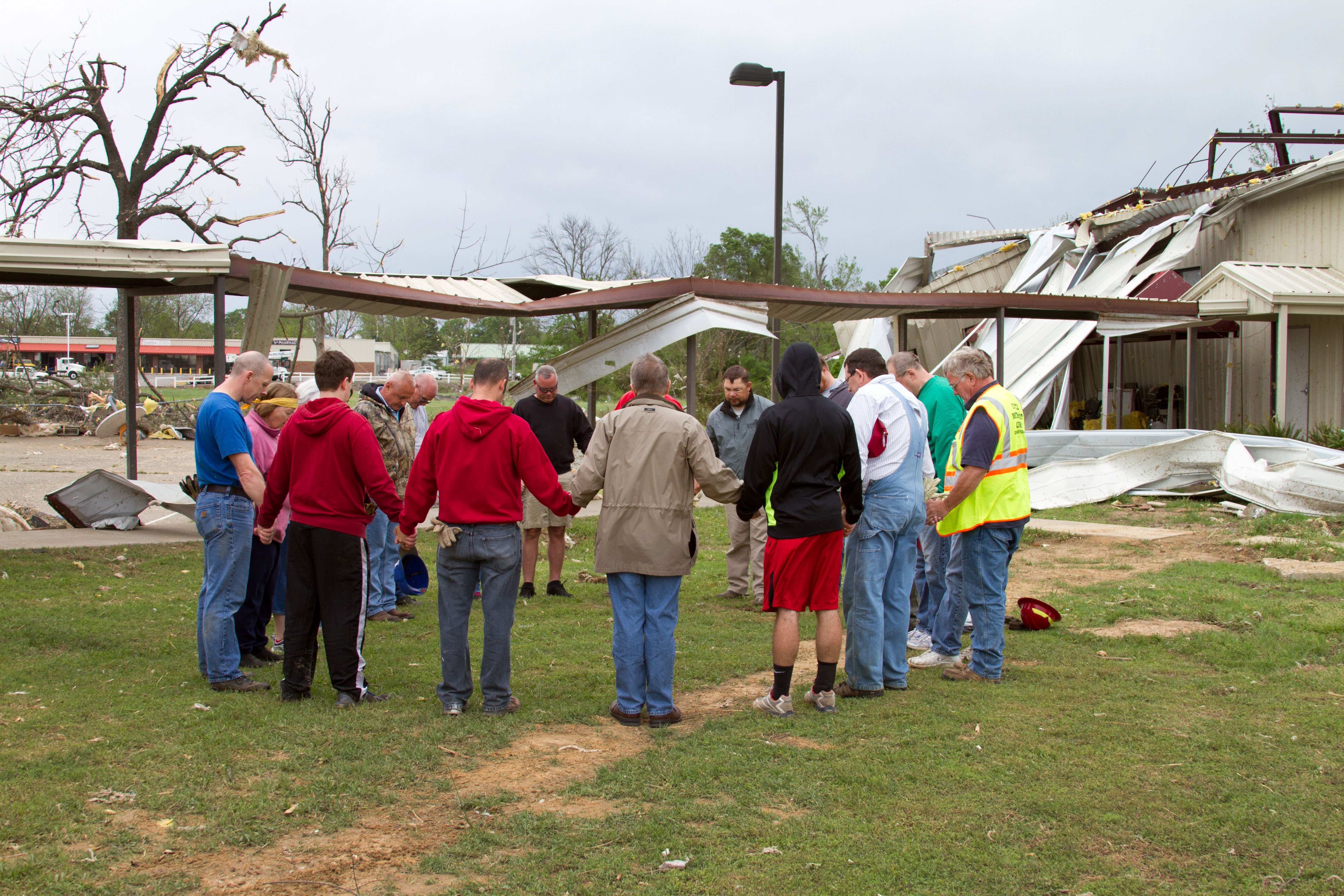 Bishop Gary Mueller (in brown jacket, back to the camera) prays for and with members of Vilonia UMC who are helping with clean-up on April 29, 2014, in the wake of the tornado that ripped through the central Arkansas town two days earlier. Photo by Amy Forbus, Arkansas United Methodist.